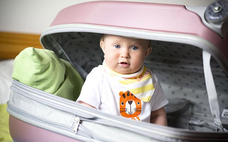 Beba sedi u koferu